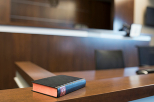 Bible on witness stand in empty courtroomの写真素材 [FYI02708623]
