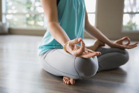 Woman in lotus position practicing mudra meditationの写真素材 [FYI02708656]
