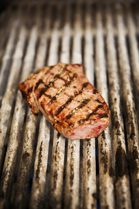 Close up high angle view of a steak on a griddle.の写真素材 [FYI02708692]