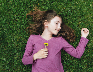 A ten year old girl lying, holding a dandelion flower.の写真素材 [FYI02708697]