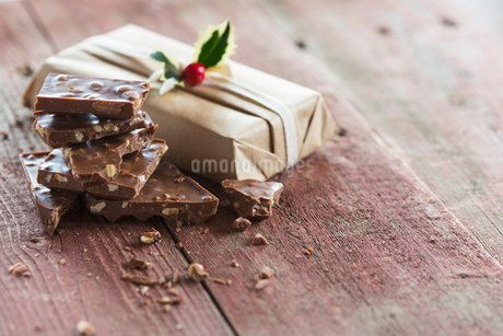 Pieces of chocolate candy bar near Christmas giftの写真素材 [FYI02708754]