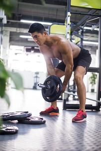 Young man lifting barbell at gymの写真素材 [FYI02708770]