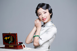 Young beautiful woman in traditional cheongsam dressing up herselfの写真素材 [FYI02708859]