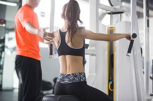 Young woman working with trainer at gymの写真素材 [FYI02708861]