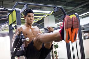 Young man exercising at gymの写真素材 [FYI02708871]