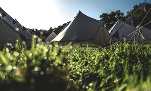 Glamping bell tents, traditional canvas tents in an enclosure on the camping grounds at an outdoor mの写真素材 [FYI02708885]