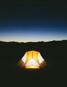 Illuminated camping tent in vast desert at dusk, Black Rock Desert, Nevadaの写真素材 [FYI02708888]
