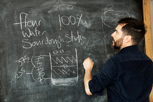 Baker standing in front of a blackboard, writing a recipe for bread.の写真素材 [FYI02708900]