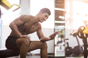 Young man using smart phone in gymの写真素材 [FYI02708985]