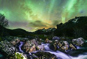 Aurora borealis over landscape with small river near theの写真素材 [FYI02709029]