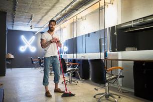 Portrait hipster hairstylist sweeping hair salon floor broomの写真素材 [FYI02709040]