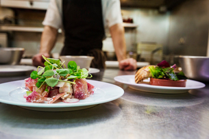 Close up of two plates of food in a kitchen, chef wearing apron standing in background.の写真素材 [FYI02709053]