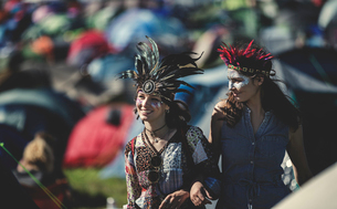 Two smiling young women at a summer music festival face painted, wearing feather headdress, standingの写真素材 [FYI02709100]