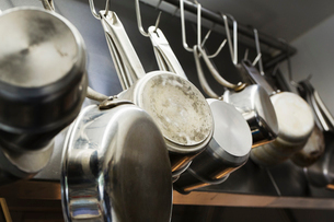 Close up of stainless steel pots and pans hanging on metal hooks on a shelf in a restaurant kitchen.の写真素材 [FYI02709102]