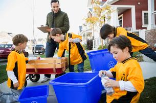 Coach and boys sports team gathering recycling neighborhoodの写真素材 [FYI02709109]