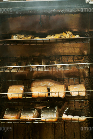 Fish fillets on racks in a fish smoker.の写真素材 [FYI02709111]