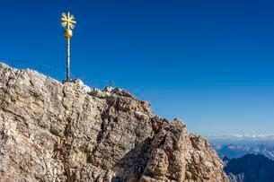 Gilded summit cross, Zugspitze, view towards Tyrol behindの写真素材 [FYI02709174]