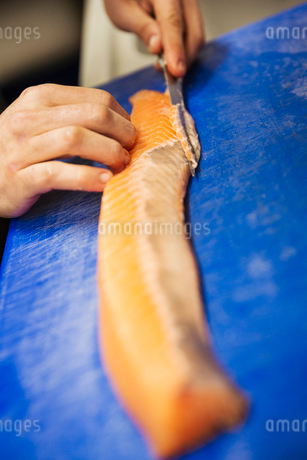 Close up high angle view of person, cutting a fillet of salmon on a blue chopping board.の写真素材 [FYI02709196]