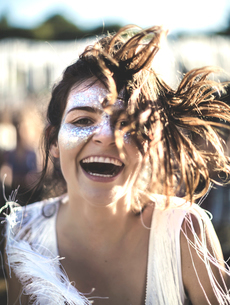 Young woman with long brown hair at a summer music festival face painted, smiling at camera.の写真素材 [FYI02709282]