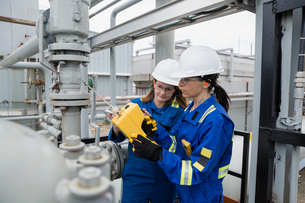 Female workers checking equipment at gas plantの写真素材 [FYI02709329]