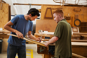 Two men standing at a workbench in a boat-builder's workshop, working on piece of wood.の写真素材 [FYI02709335]