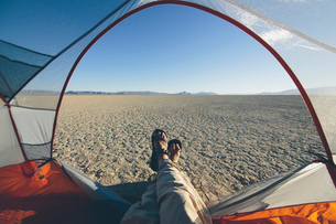 Man reclining in camping tent, expansive desert and playa in distance, Black Rock Desert, Nevadaの写真素材 [FYI02709482]