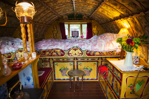 The interior of a traditional gypsy caravan with raised bed and cupboards, bow top roof and stove.の写真素材 [FYI02709483]