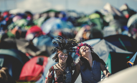 Two smiling young women at a summer music festival face painted, wearing feather headdress, standingの写真素材 [FYI02709516]