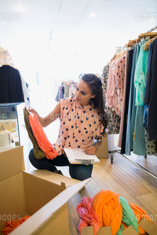 Business owner unpacking new inventory in clothing shopの写真素材 [FYI02709542]
