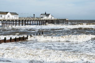 Seascape with waves rolling onto beach near groyne and white wooden buildings on a pier.の写真素材 [FYI02709548]