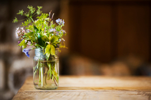 Close up of glass jar with small bunch of wild flowers on a wooden table.の写真素材 [FYI02709573]