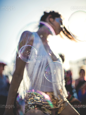 Young woman at a summer music festival wearing golden sequinned hot pants, dancing among the crowd.の写真素材 [FYI02709660]