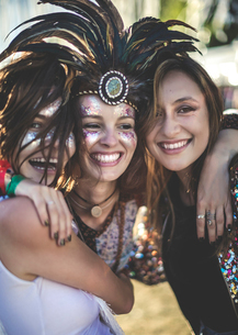 Three young women at a summer music festival wearing feather headdress and faces painted, smiling atの写真素材 [FYI02709682]