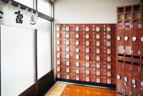 The interior of a public bath house, with rows of shoe lockers and clothes lockers.の写真素材 [FYI02709703]