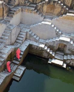 High angle view of two women wearing pink saris walking up stairwell around water pool of an ancientの写真素材 [FYI02709715]