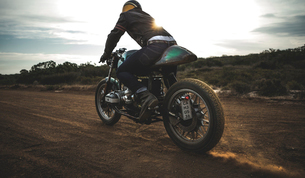 Rear view of man wearing crash helmet riding cafe racer motorcycle on a dusty dirt road.の写真素材 [FYI02709766]