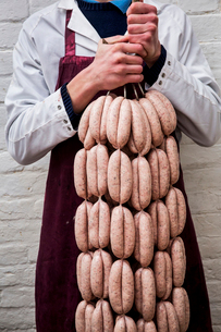 Man wearing apron holding large number of freshly made sausages hanging from hooks.の写真素材 [FYI02709778]