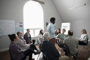 Man talking at support group in community centerの写真素材 [FYI02709837]