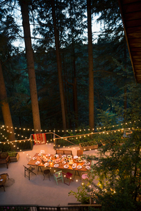 String lights illuminating balcony and long dining table in woodsの写真素材 [FYI02709875]