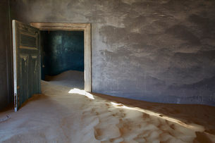 An abandoned building, an open door and drifts of sand encroaching into the room from the rest of thの写真素材 [FYI02709887]