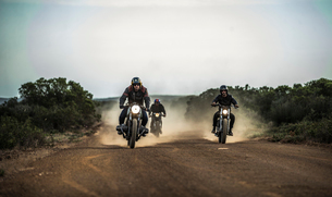 Three men riding cafe racer motorcycles along dusty dirt road.の写真素材 [FYI02709892]