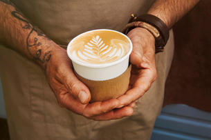 Close up of man with tattoo on his arm holding paper cup with cafe latte.の写真素材 [FYI02709899]