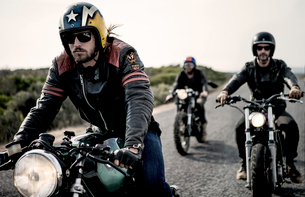 Three men wearing open face crash helmets and sunglasses riding cafe racer motorcycles along rural rの写真素材 [FYI02709911]