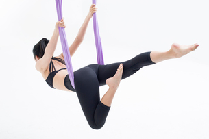 Young Chinese woman practicing aerial yogaの写真素材 [FYI02709950]
