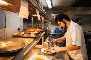 Chef standing in a restaurant kitchen at a counter, holding sauce pan, plating food.の写真素材 [FYI02709951]