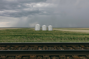 Grain silos and storm clouds over vast areas of farmland and prairie, train tracks in foregroundの写真素材 [FYI02709979]