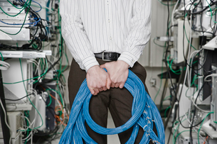 Male computer technician holding CAT 5 cables and standing in the aisle of a computer server farm.の写真素材 [FYI02709982]