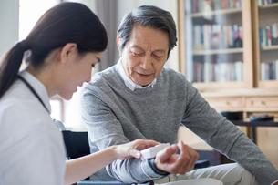 Nursing assistant taking care of senior manの写真素材 [FYI02710040]