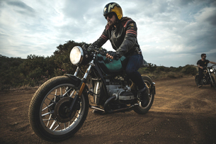 Man wearing open face crash helmet and sunglasses riding cafe racer motorcycle on a dusty dirt road.の写真素材 [FYI02710052]