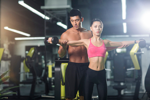 Young woman working with trainer at gymの写真素材 [FYI02710062]